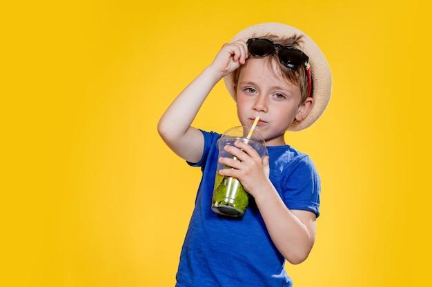 Милый мальчик пить коктейль мохито из пластикового стаканчика на желтом фоне студии.