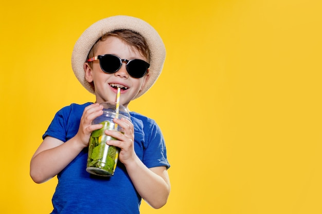 Cute boy drink mojito cocktail from plastic cup over yellow studio background.