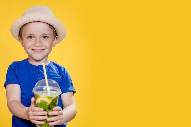Милый мальчик пьет лимонад из пластикового стаканчика