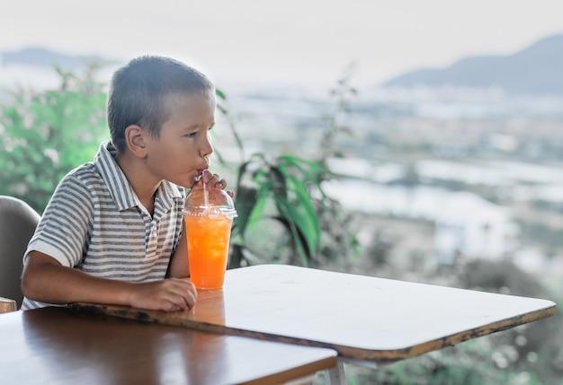 야외 카페에서 주스를 마시는 귀여운 소년