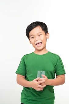Cute boy drinking milk on light