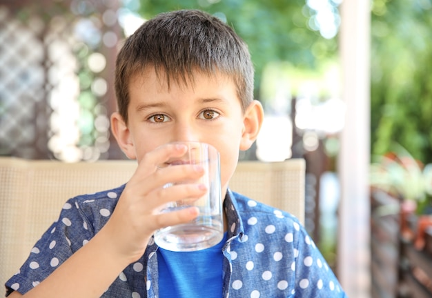 Милый мальчик пьет воду в кафе