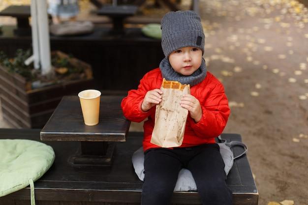 Милый мальчик ест фаст-фуд и пьет какао, маленький кавказский мальчик и вкусную уличную еду