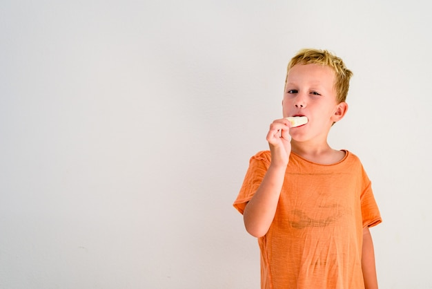 Cute boy eating an ice cream in white background.