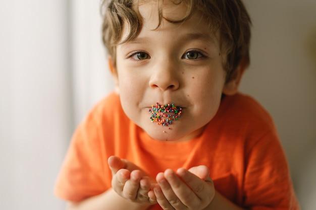 Милый мальчик ест и играет с пасхальными брызгами