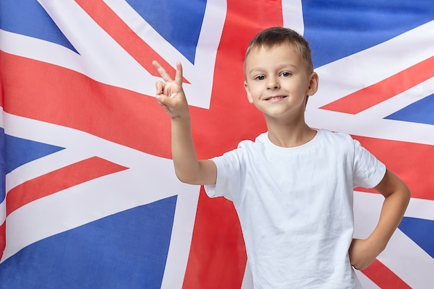 The cute boy folded his fingers in the shape of a v against the of the british flag