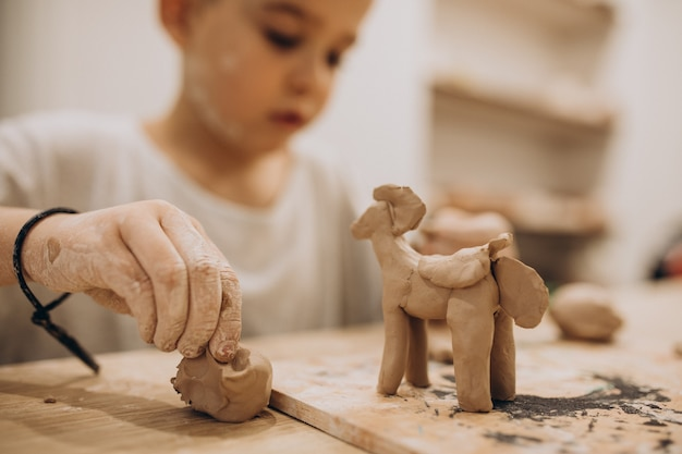 Cute boy forming toys from clay