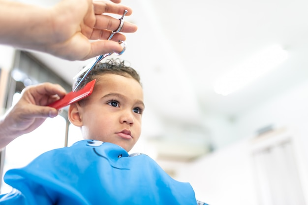 Cute boy getting a hair cut in a barber shop beauty concept