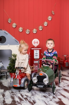 Cute boy and girl play and ride on toy cars.