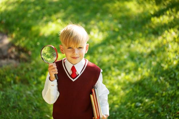 かわいい男の子が学校に戻ります。最初の学校の日に本とルーペを持つ子供