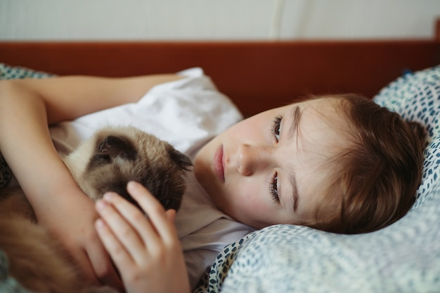 Cute boy and his cat cuddling in the bed at morning. child and his cat at home. kids and pets. lovely kid with his animal. cozy home at morning. child's friendship with domestic cat.
