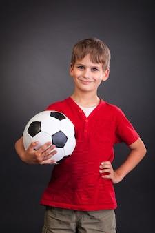 Милый мальчик держит футбольный мяч