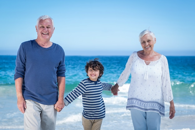 Cute boy holding his grandparents hands