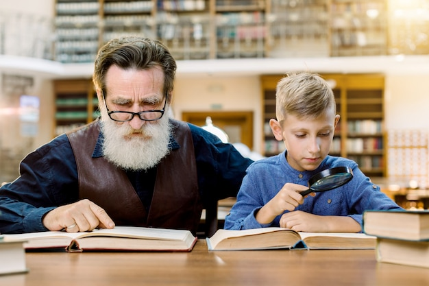 Cute boy holding magnifying glass reading book with his handsome grandfather, sitting at the table in old stylish library, on background of vintage book shelves. world book day concept