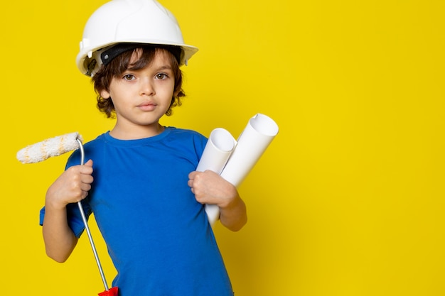 Cute boy holding paint brush and paper plans in white helmet and blue t-shirt on yellow