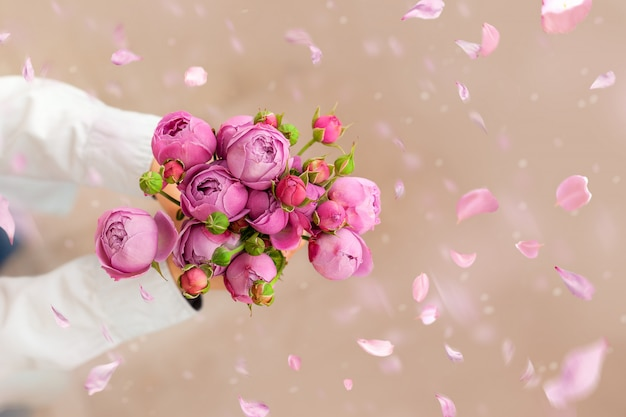 Cute boy holding pink roses bunch flowers for mother a with falling petals. greeting card for mother's day.