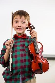 教室で弓でバイオリンを保持しているかわいい男の子