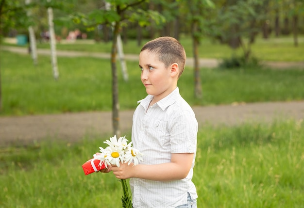 腕にリボンの弓で包まれたギフトボックスを保持しているかわいい男の子。