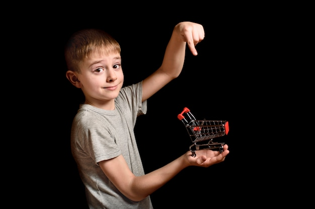 Cute boy holds small metal shopping trolley in hand and points to it with index finger.