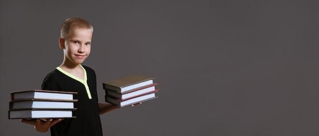 검은색 티셔츠를 입은 귀여운 소년은 회색 배경에 책 더미를 들고 있다