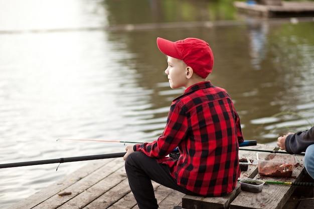 호수에서 낚시 하는 체크 무늬 셔츠에 귀여운 소년. 여름 야외 활동 개념입니다.