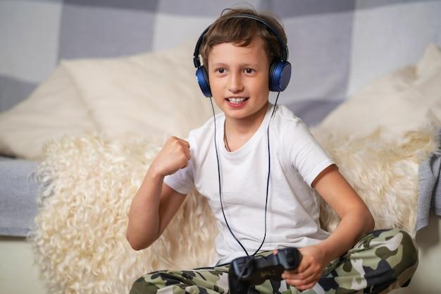 ゲームでの勝利に満足して、ジョイスティックを手にしたヘッドフォンでかわいい男の子