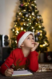 赤いセーターと赤いサンタ帽子のかわいい男の子がサンタに手紙を書く