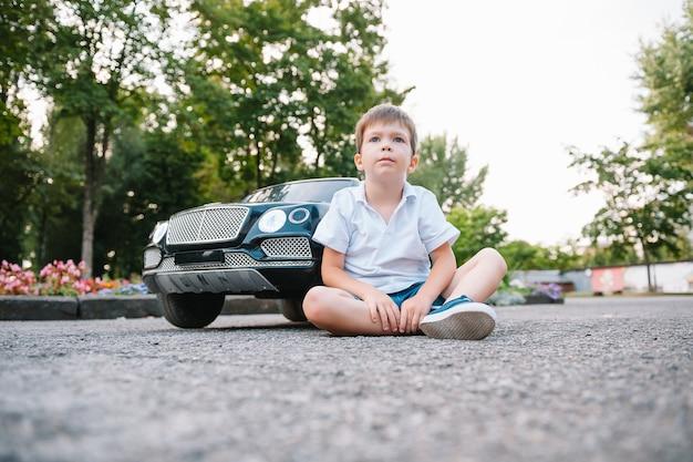 Милый мальчик в езде на черном электромобиле в парке