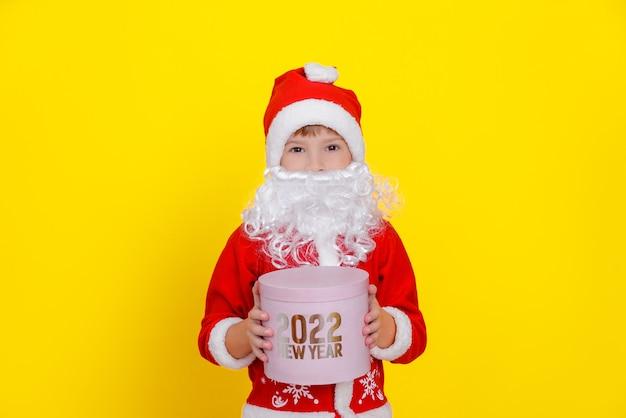 산타클로스 옷을 입고 턱수염을 기른 귀여운 소년은 손에 분홍색 둥근 선물 상자를 들고 있다