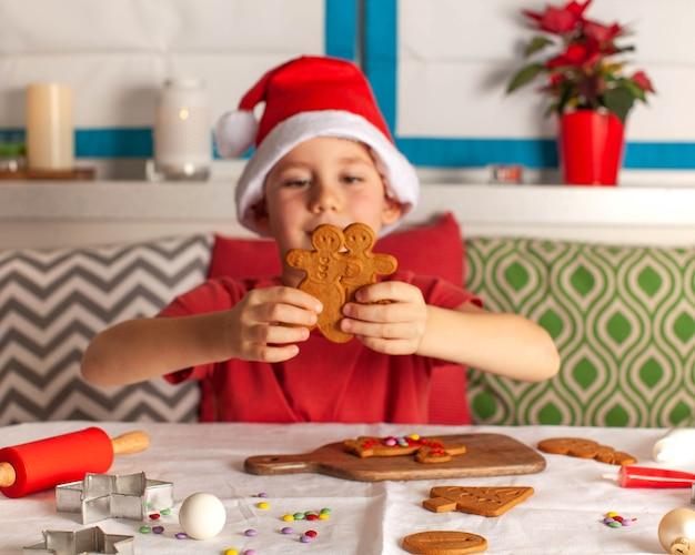 サンタクロースの帽子をかぶったかわいい男の子がテーブルのクリスマスライトでジンジャーブレッドを作ります