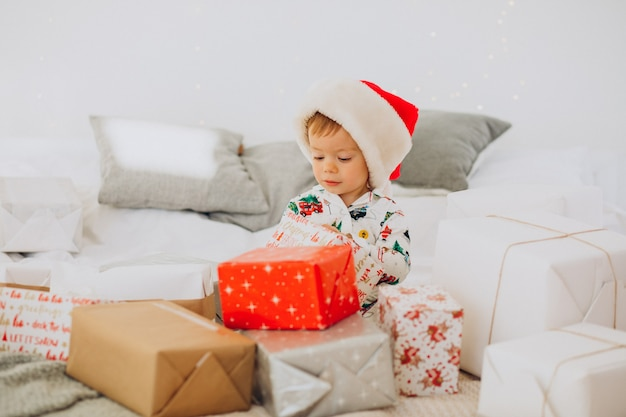 Милый мальчик в новогодней шапке открывает подарки на рождество