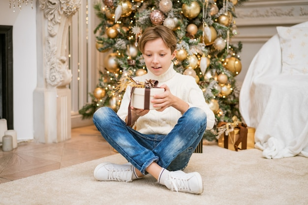 Симпатичный мальчик в свитере сидит у елки с подарками кавказский подросток дома с праздничным ...