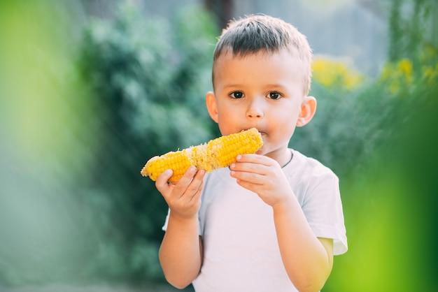 삶은 옥수수를 먹고 정원에서 귀여운 소년