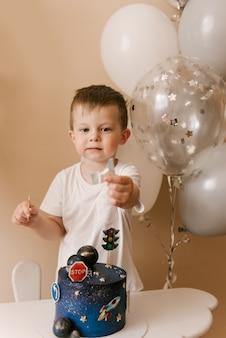 Милый мальчик празднует свой день рождения и ест вкусный красивый торт, фото ребенка с воздушными шарами