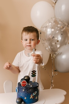 Cute boy is celebrating his birthday and eating a delicious beautiful cake, photo of a child with balloons