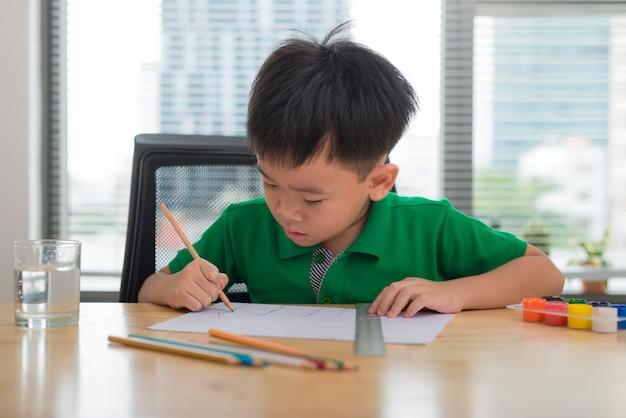 かわいい男の子が白で隔離された色鉛筆を使って描いています