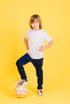 かわいい男の子は、黄色の背景に分離された本革で作られたサッカーボールを保持しています