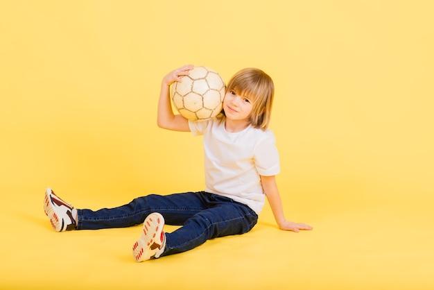 かわいい男の子は、黄色に分離された本革で作られたサッカー ボールを持っています。