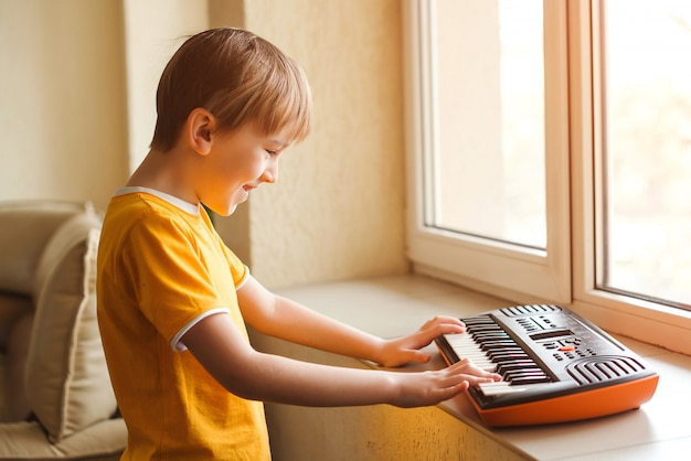 Cute boy is playing on a synthesizer at home. ckids hobbies and leisure.