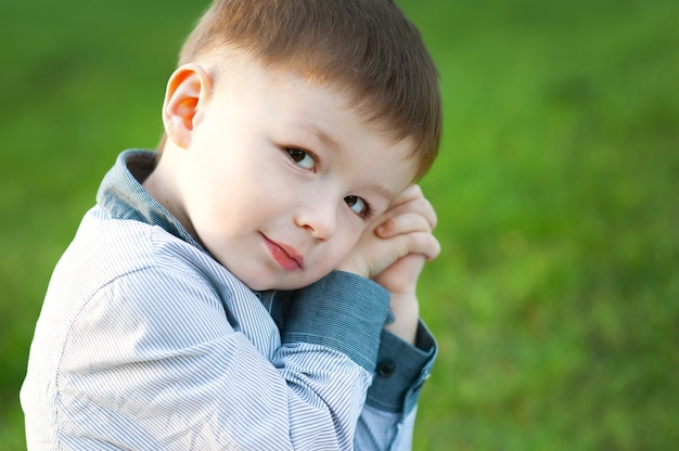 Cute boy is sitting on green grass. he is waiting.  childrens happy
