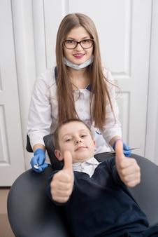 Милый мальчик сидит в кресле стоматолога и показывает палец вверх жестами хорошего класса.