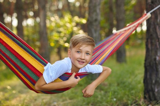 かわいい男の子がハンモックに座っています。
