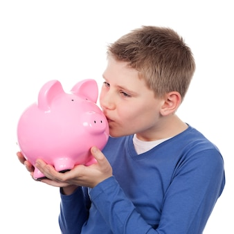Cute boy kissing pink piggybank on white space