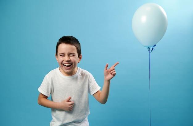Милый мальчик смеется и показывает пальцем на воздушном шаре