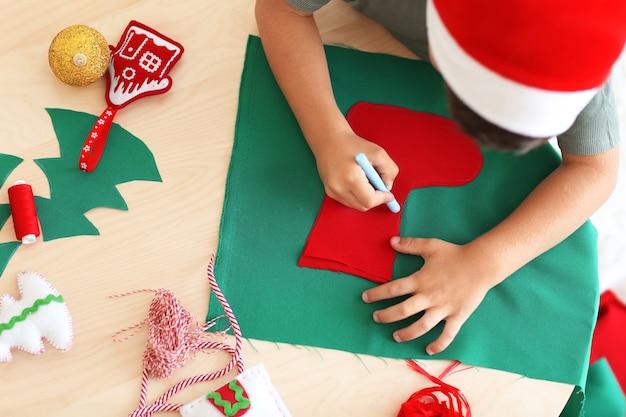 테이블에 펠트에서 크리스마스 양말을 만드는 귀여운 소년