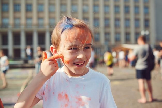Милый мальчик раскрашен в цвета фестиваля холи. счастливое детство. предварительно предназначенный для подростков мальчик, играя с красочным порошком. концепция индийского фестиваля холи. празднование холи.