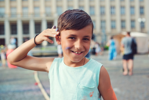 ホーリー祭の色で描かれたかわいい男の子。幸せな子供時代。カラフルな粉で遊んでいる10代前の少年。インドのお祭りホーリーのコンセプト。ホーリー祭。
