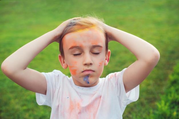 ホーリー祭の色で描かれたかわいい男の子。幸せな子供時代。カラフルな粉で遊んでいる10代前の少年。