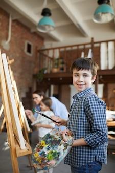 Милый мальчик, рисующий в мольберте