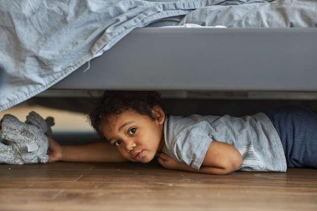 Cute boy peeking out from under the bed